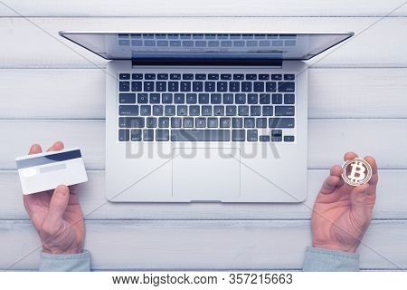 Bitcoin Vs Bank Card Online Shopping And Trading Concept. Man Decides How To Pay. Toned Picture.