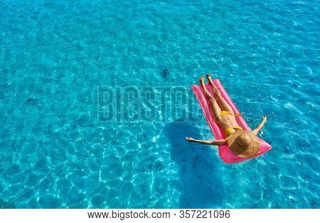 Woman relaxing on inflatable mat float at the beach