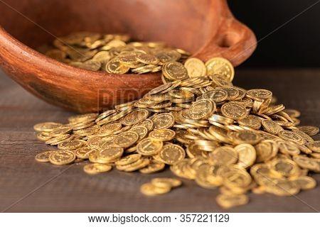 Cascade Of Small Golden Coins From A Crock Pot