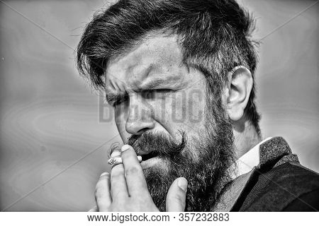Bearded Hipster Smoking Cigarette Sky Background. Guy Cigarette Enjoy Nicotine Influence. Cigarettes