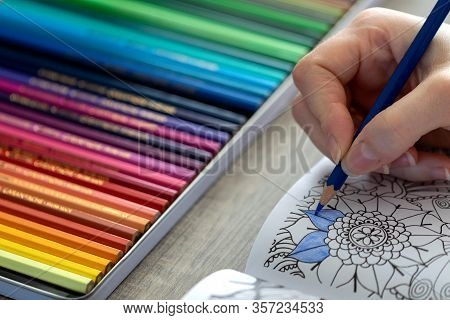 A Portrait Of A Person Holding A Blue Color Pencil In His Or Her Hand, While Coloring In A Coloring
