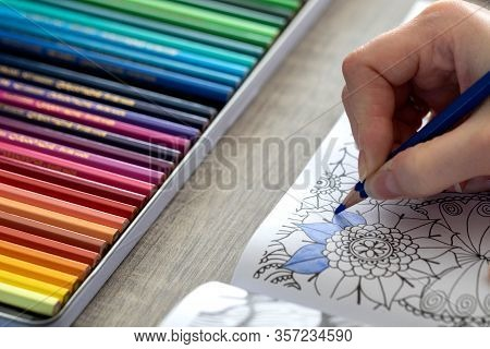 A Portrait Of An Adult Person Coloring In A Coloring Book For Adults With A Blue Colored Pencil In T