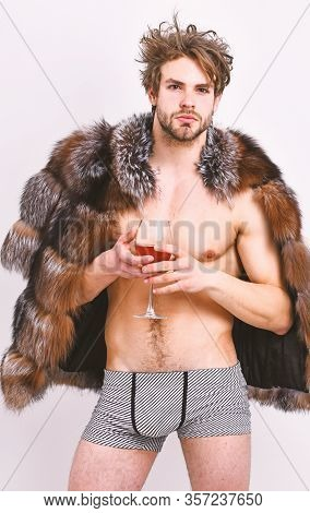Richness And Luxury Concept. Guy Attractive Rich Posing Fur Coat On Naked Body. Rich Athlete Enjoy H