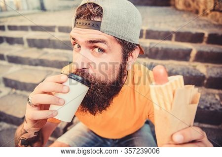 Drink Something Different. Caucasian Hipster Enjoy Drinking Takeaway Drink With Hot Dog. Bearded Man