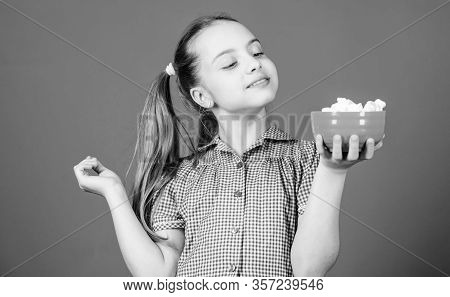 Calorie And Diet. Girl Smiling Face Hold Bowl Sweets Marshmallows In Hand Blue Background. Kid Girl