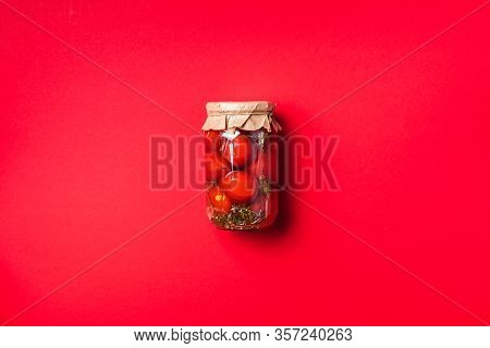 Pickled Tomatoes In Jar On Red Background. Top View. Flat Lay. Copy Space. Canned And Preserved Vege