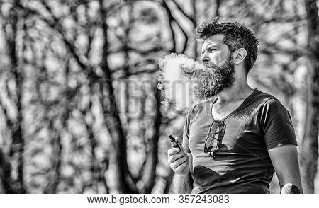 Stress Relief Concept. Bearded Man Smoking Vape. White Clouds Of Flavored Smoke. Smoking Electronic