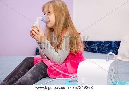 Child With Asthmatic Problems Is Take Inhalation With Mask On Her Face, Home Therapy.
