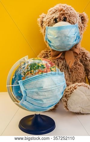 Teddy Bear Toy Wearing Medical Face Mask And Holding Earth World Globe With Protective Mask On Yello