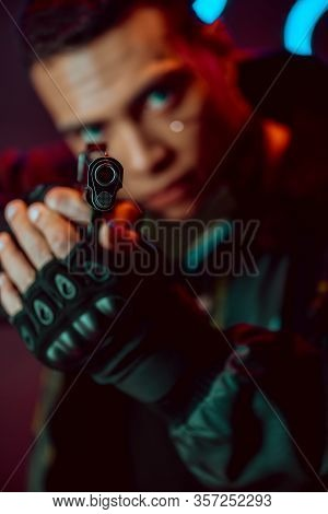 Selective Focus Of Gun In Hands Of Bi-racial Cyberpunk Player