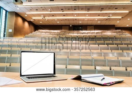Photo of laptop on professor desk with lesson plan in empty classroom