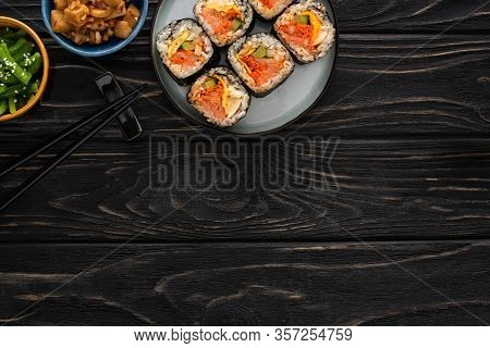 Top View Of Chopsticks Near Plate With Gimbap And Korean Side Dishes On Wooden Surface