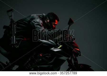 Profile Of Armed Bi-racial Cyberpunk Player In Mask Riding Motorcycle On Grey