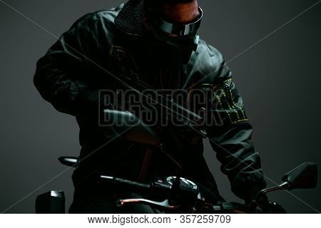 Selective Focus Of Armed Bi-racial Cyberpunk Player In Mask And Futuristic Glasses Riding Motorcycle