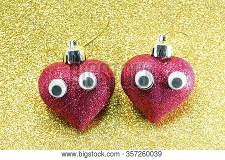 Two Big Hearts With Eyes And Golden Glittery Background Symbol Of Love