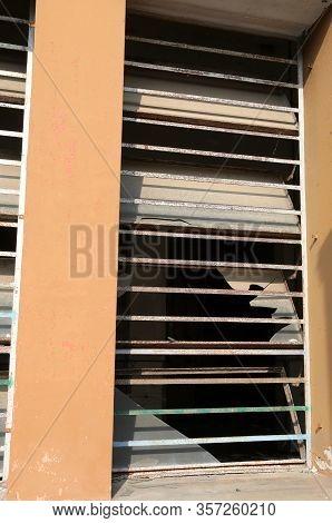 Broken Window With Broken Glass Of An Abandoned Building After Vandalism