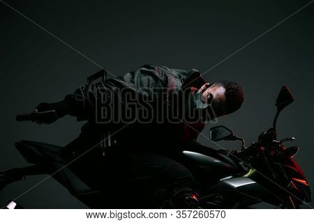 Armed Bi-racial Cyberpunk Player In Mask Riding Motorcycle And Holding Gun On Grey