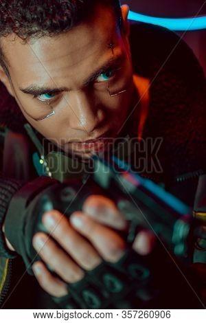 Selective Focus Of Armed Bi-racial Cyberpunk Player With Metallic Plates On Face Holding Gun