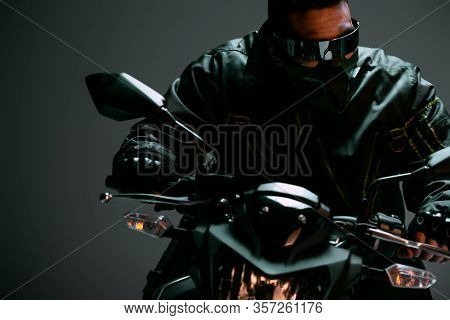 Selective Focus Of Bi-racial Cyberpunk Man In Mask And Futuristic Glasses Riding Motorcycle On Grey
