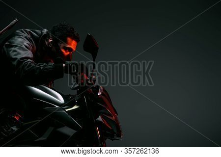 Side View Of Dangerous Bi-racial Cyberpunk Player In Mask Riding Motorcycle On Grey