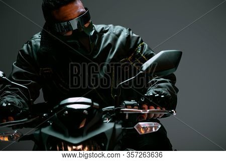 Selective Focus Of Bi-racial Cyberpunk Player In Mask And Futuristic Glasses Riding Motorcycle On Gr