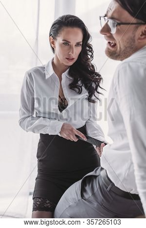 Passionate Businesswoman Touching Belt Of Discouraged Colleague While Seducing Him In Office