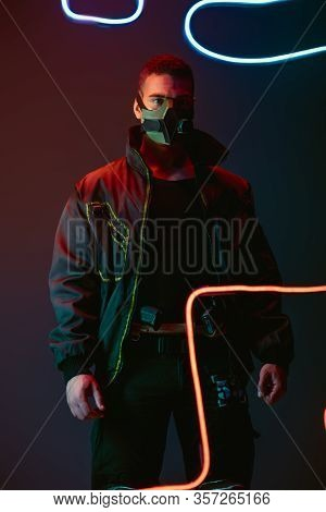 Armed And Bi-racial Cyberpunk Player In Protective Mask Standing Near Neon Lighting On Black
