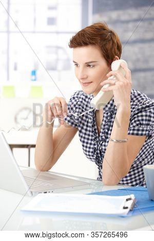 Home office - Assistant sitting at desk looking at laptop computer screen, answering landline phone, smiling.