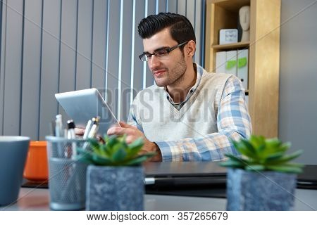 Home office - Young man sitting at desk at home, using tablet computer.