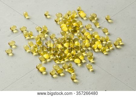 Pile Of Transparent Capsules Of Golden Yellow Color Lies On Light Gray Modern Background. Oil Filled
