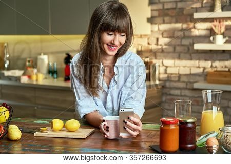 Stay at home - Happy young attractive white woman in man's shirt using mobile phone while having breakfast in kitchen at home at the morning, smiling.