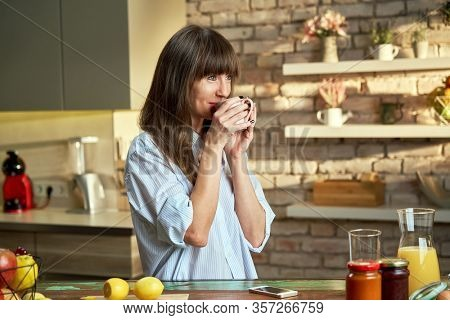 Stay at home - Happy white woman at home drinking coffee at morning in kitchen.