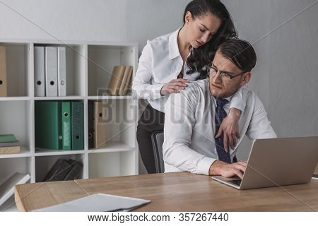 Sexy Businesswoman Embracing Confused Colleague Sitting At Workplace