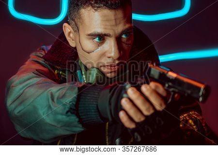 Selective Focus Of Dangerous Bi-racial Cyberpunk Player With Gun On Black With Neon Lighting