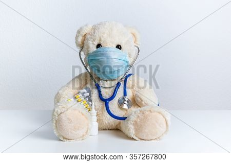 Cute Teddy Bear Doctor With Protective Medical Mask, Stethoscope And Medicine. Concept Of Pediatric