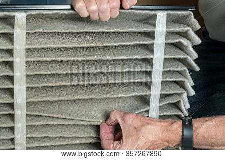 Senior Caucasian Man Looking At The Dust In Folded Dirty Air Filter In The Hvac Furnace System In Ba