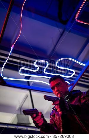Low Angle View Of Armed Bi-racial Cyberpunk Player Holding Guns Near Neon Lighting