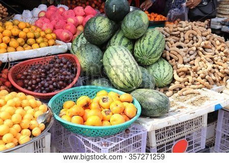 Different ripe fruits - watermelon, grapes, persimmon, tamarin, mandarin, street market, Cambodia