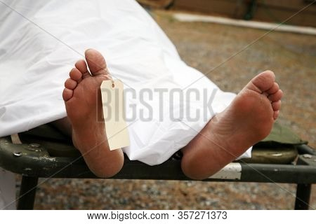 Coronavirus19. COVID-19. Coronavirus19 Dead Body, with an identification tag - blank sign attached to a toe. Covered with a white sheet. Dead Human due to COVID-19 Infection. Dead Person Coronavirus19