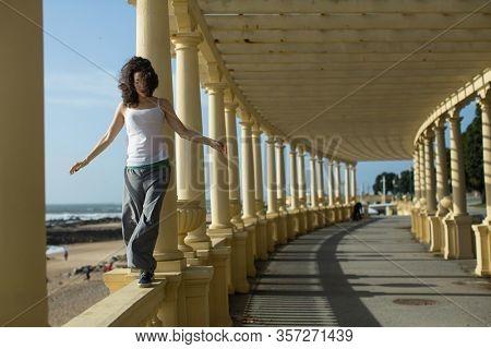 Beautiful asian mixed-race woman walks along the railing of the ocean promenade.