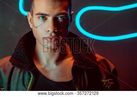 Handsome And Bi-racial Cyberpunk Man Looking At Camera Near Neon Lighting On Black
