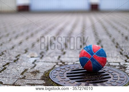 Small Basketball For Children Lying On A Gully Cover In A Deserted Backyard