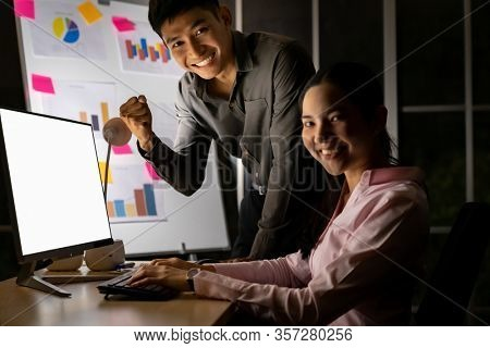 Young adult asian businessman and businesswoman work with analysis graph on white board late at night in their office with desktop computer. Using as hard working and working late concept.