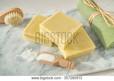 Natural soap homemade bars for exfoliation skincare with epsom salts and ramie towel scrubbing brush on marble top.