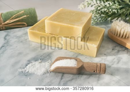 Handmade natural soap bars with epsom salt and scrubbing towel for skincare exfoliation spa therapy. Top view of olive oil soaps on marble background.
