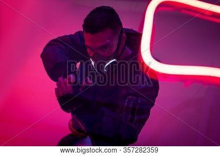Overhead View Of Armed Bi-racial Cyberpunk Player In Mask Holding Gun Near Neon Lighting