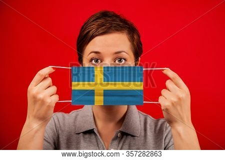 Coronavirus Covid-19 In Sweden. Woman In Medical Protective Mask With The Image Of The Flag Of Swede