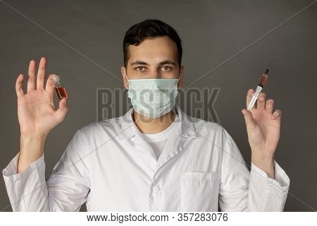 A Medical Worker Holds A Vaccine Against A Deadly Virus. Photo On A Grey Background