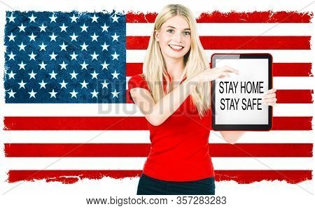 Stay Home Stay Safe. Corona Virus Pandemie Concept. Young Woman With American National Flag On The B