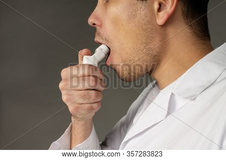 A Person Uses A Cough Inhaler To Beat The Disease. Photo On A Grey Background